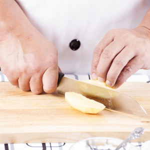 Chef Cutting Potato On Wooden Broad