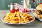 Tasty sandwiches and french fries on plate, on wooden background