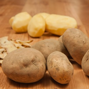 White peeled potatos. Potato peelings.  Next to are peelings