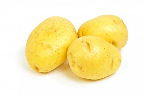 Raw Yukon Gold potatoes on white background horizontal format